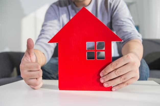 Les hommes d'affaires tiennent le modèle de maison en main