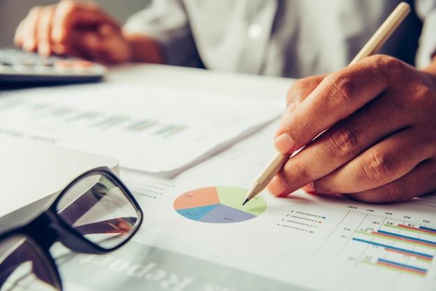 Les hommes d'affaires travaillent sur des comptes dans l'analyse commerciale avec graphiques et documentation