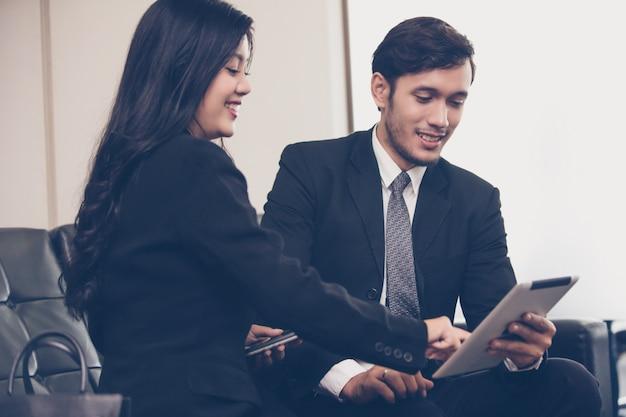 Hommes d'affaires utilisant un cahier pour leurs partenaires commerciaux discutant de documents et d'idées lors d'une réunion