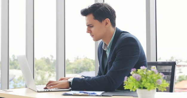 Les hommes d'affaires utilisant un ordinateur portable et remplissent sérieusement le travail accompli jusqu'au mal de tête