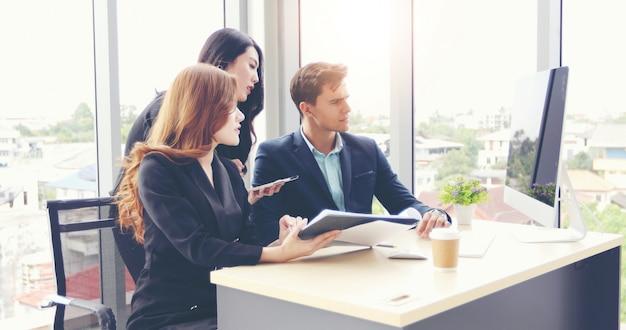 Hommes d'affaires et utilisation d'un ordinateur portable et d'une tablette pour discuter de documents et d'idées en réunion