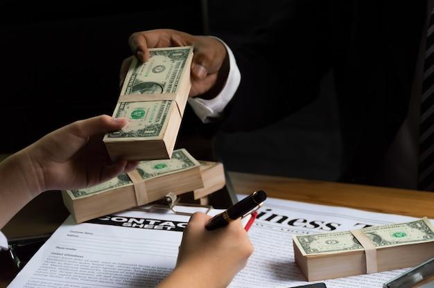 Les hommes d'affaires utilisent l'argent pour acheter d'autres personnes en échange de la signature de contrats