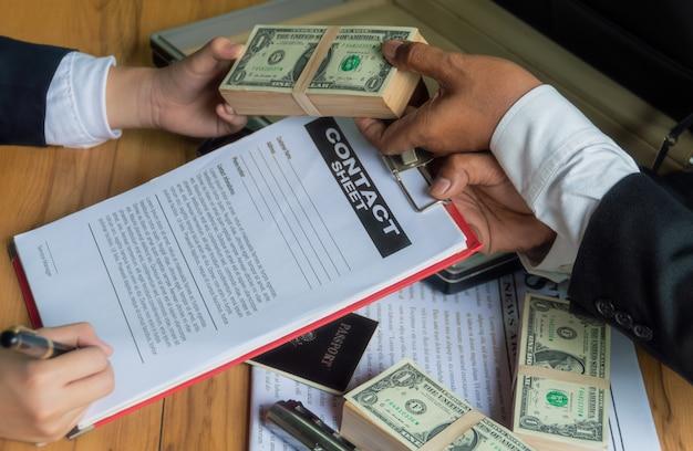 Les hommes d'affaires utilisent de l'argent pour acheter d'autres personnes en échange de la signature de contrats.