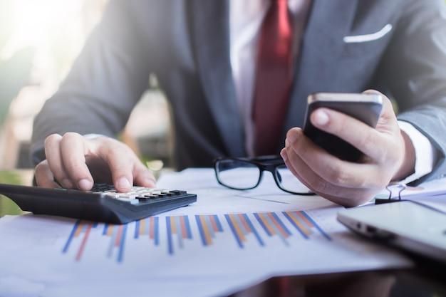 Les hommes d'affaires utilisent la calculatrice pour calculer et analyser les bénéfices de l'entreprise