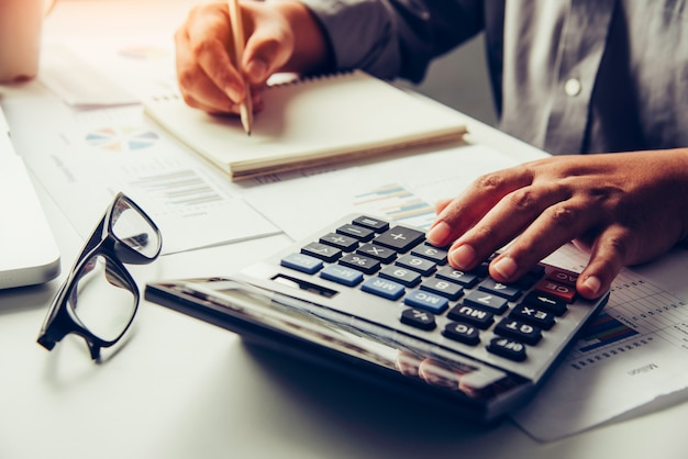 Les hommes d'affaires utilisent une calculatrice pour calculer le revenu de l'entreprise.
