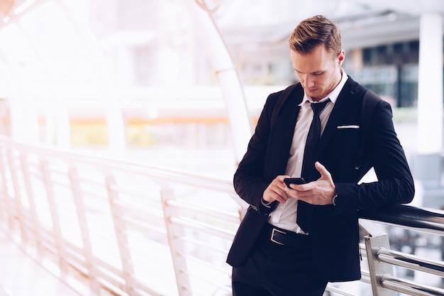 Les hommes d'affaires utilisent les smartphones pour appeler des voitures.
