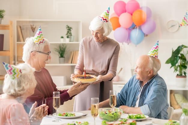 L'un des hommes âgés de prendre une assiette avec une tarte d'anniversaire maison avec une bougie allumée apportée par sa femme