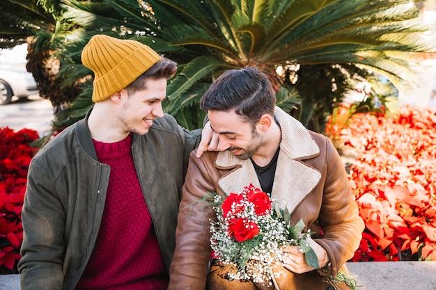 Hommes amoureux avec bouquet dans le parc
