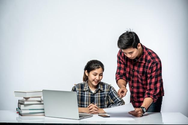 Les hommes apprennent aux femmes à travailler avec des ordinateurs portables au travail.