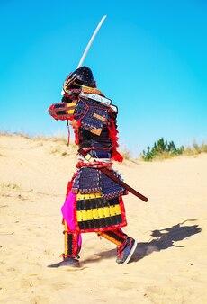 Hommes en armure de samouraï avec épée courant sur le sable