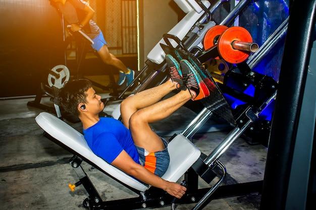 Les hommes asiatiques exercent le style de vie de machine de presse de jambe