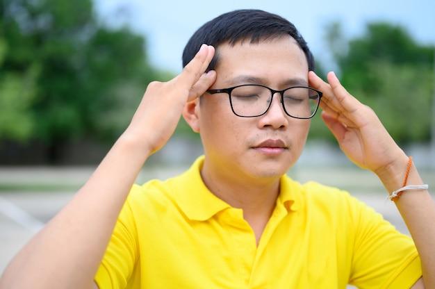 Les hommes asiatiques portent des chemises jaunes avec le stress, la fatigue oculaire.