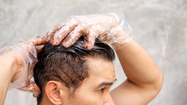 Les hommes asiatiques teignent la couleur de ses cheveux sur un fond gris.