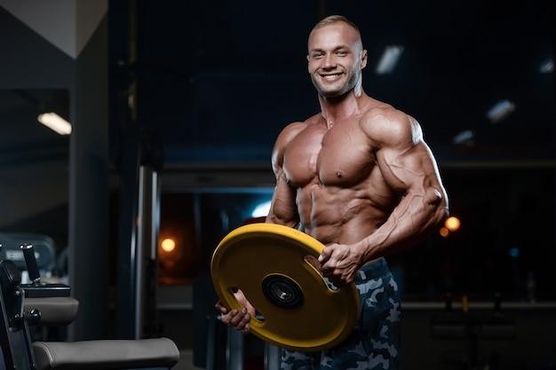 Hommes athlétiques bodybuilder forts et brutaux pompant les muscles avec des haltères