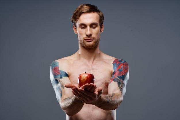 Hommes athlétiques musculation fitness presse pompé les muscles du bras tatouage pomme rouge