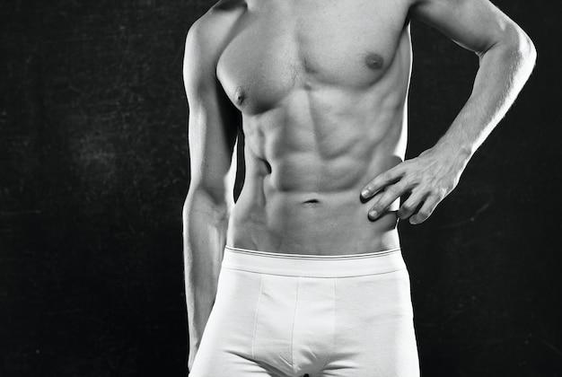 Les hommes athlétiques en short blanc ont gonflé la presse posant un fond sombre de remise en forme