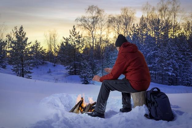 Hommes au coucher du soleil dans les bois d'hiver près d'un feu de joie. concept de solitude, d'hommes pensants.