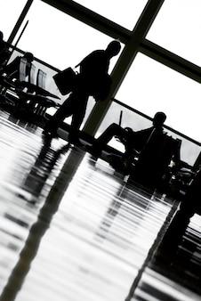Hommes au terminal de l'aéroport, vue de côté