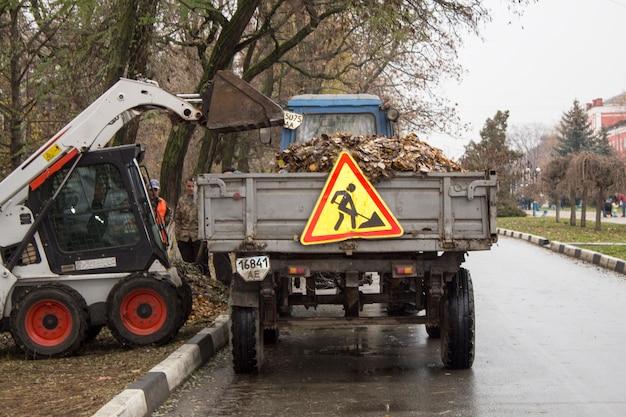 Hommes au travail. travailler sur la collecte des feuilles d'automne dans les rues. nettoyage des feuilles, chargement des feuilles sur un tracteur