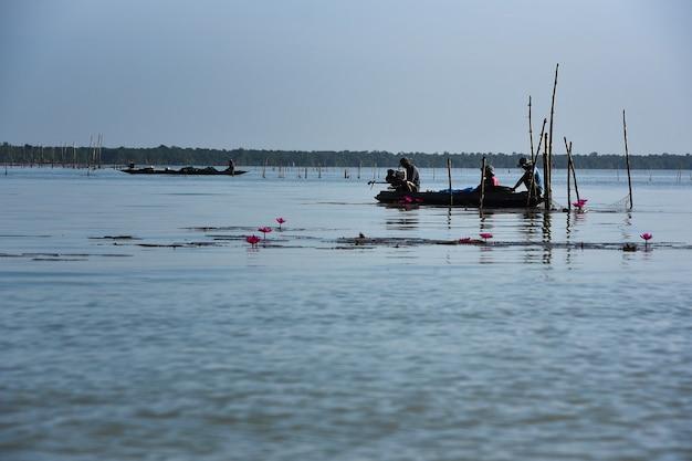 Les hommes sur le bateau font de la petite pêche dans le lac en tant qu'attraction touristique de la province de phatthalung dans le sud de la thaïlande