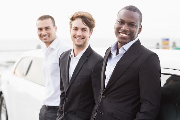 Des hommes bien habillés posant s'appuyant sur une limousine