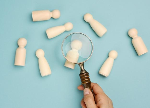 Hommes en bois et une loupe sur fond bleu. concept de recrutement, recherche d'employés talentueux et compétents, évolution de carrière, mise à plat