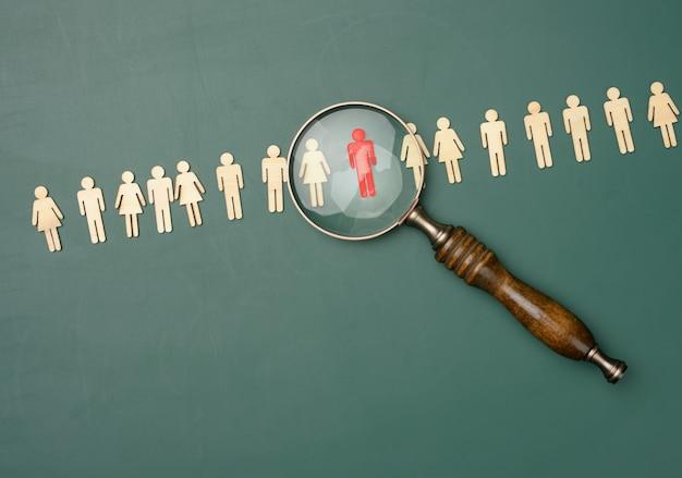 Hommes en bois et une loupe sur fond vert. concept de recrutement, recherche d'employés talentueux et compétents, évolution de carrière, mise à plat