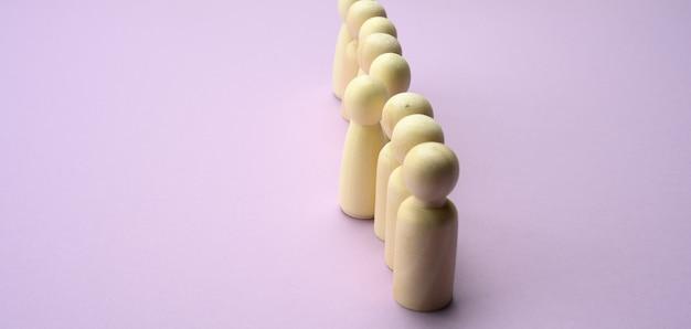 Les hommes en bois se tiennent dans une rangée, une figurine sortant devant