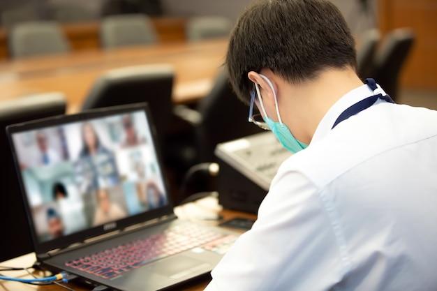 Les hommes de bureau prennent des notes pendant la réunion en ligne via l'ordinateur portable avec appel vidéo