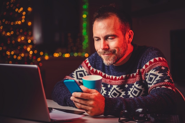 Hommes buvant du café et utilisant un téléphone intelligent