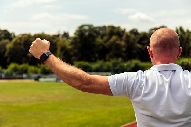 Les hommes chauves forts indiquent quelque chose sur le terrain de football. vue arrière du bel homme en t-shirt pointant.