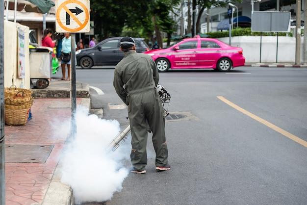 Les hommes courent dans le brouillard pour éliminer les moustiques afin de prévenir la dengue