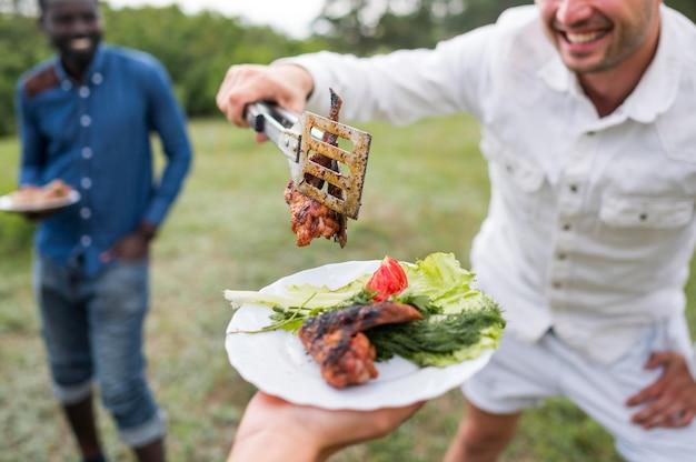 Hommes cuisine barbecue à l'extérieur