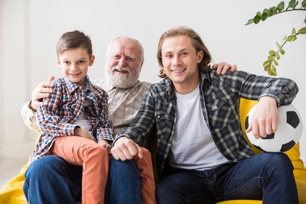 Des hommes de différentes générations regardent la télévision sur un canapé