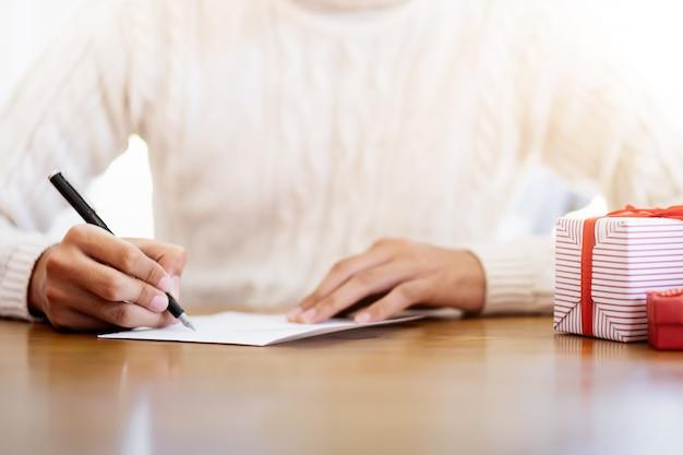 Hommes écrivant des cartes de voeux pendant noël et nouvel an.