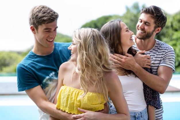 Hommes embrassant des femmes près de la piscine