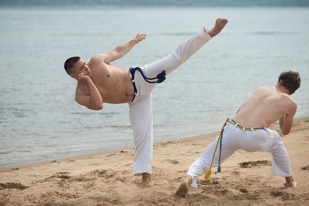 Les hommes entraînent la capoeira sur la plage - concept sur les gens, le style de vie et le sport.