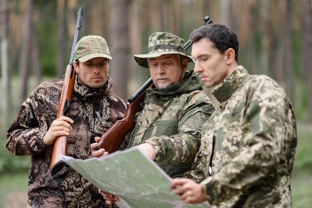 Des hommes étudient la carte lors d'une chasse en famille dans une forêt