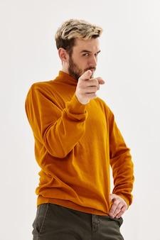 Les hommes avec une expression sérieuse pointe un doigt vers l'avant fond clair de studio de mode