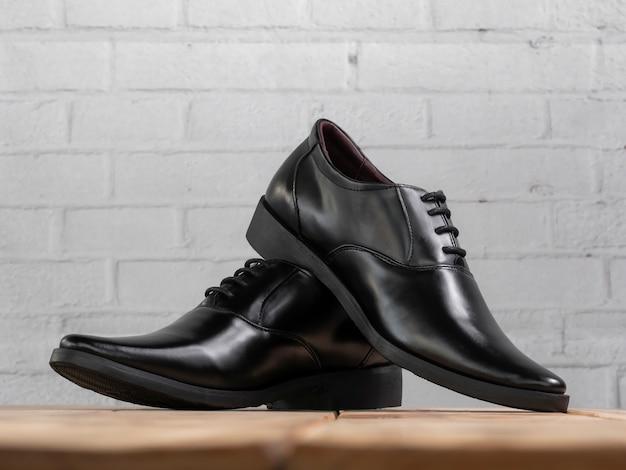 Les hommes façonnent des chaussures noires sur bois.