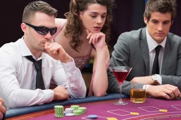 Hommes et femme assis à la table de poker