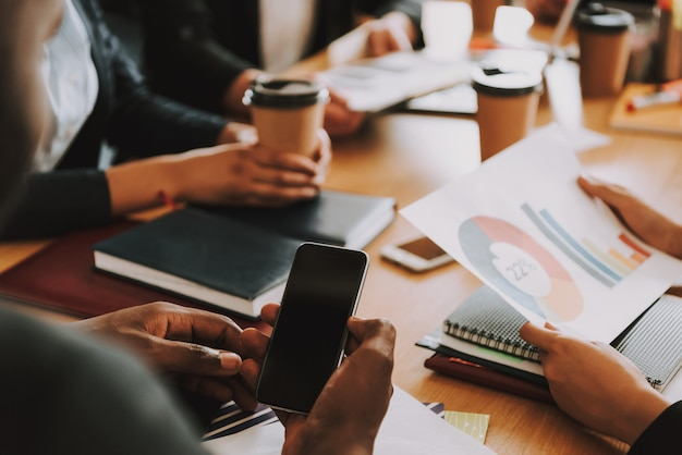 Les hommes et les femmes d'affaires font du travail à la table.
