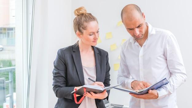 Hommes et femmes d'affaires regardant le calendrier dans le journal