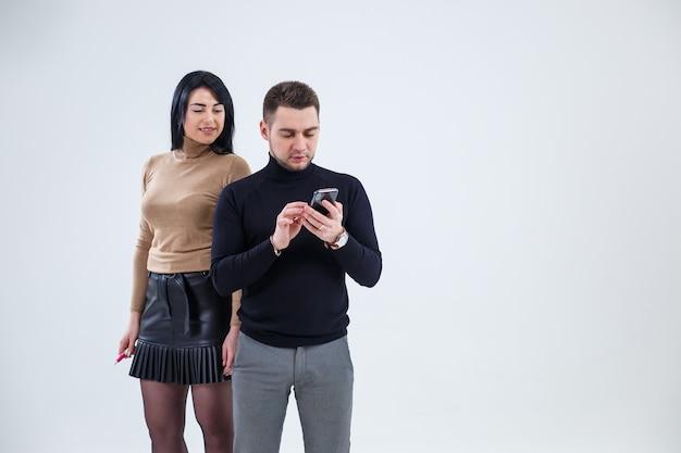Les hommes et les femmes d'affaires regardent l'écran du téléphone. debout sur un fond blanc et parler d'affaires.