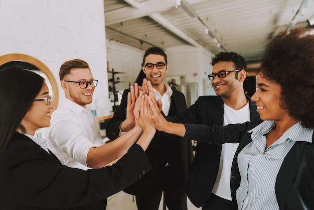 Hommes et femmes d'affaires se donnent à cinq