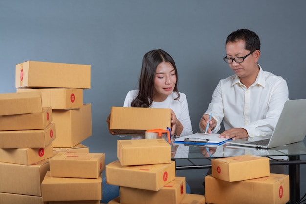 Les hommes et les femmes aident à emballer les cartons.