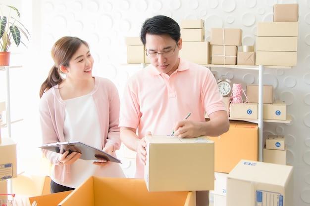 Hommes et femmes asiatiques écrivant des adresses pour livrer des colis aux clients