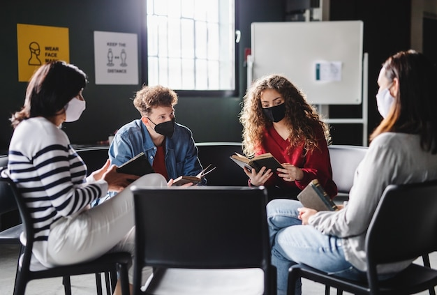 Hommes et femmes assis en cercle pendant la thérapie de groupe, lisant et parlant. notion de coronavirus.