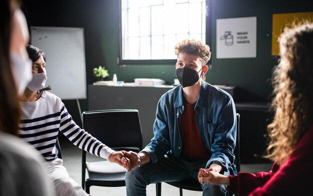 Hommes et femmes assis en cercle pendant la thérapie de groupe, se tenant la main. notion de coronavirus.