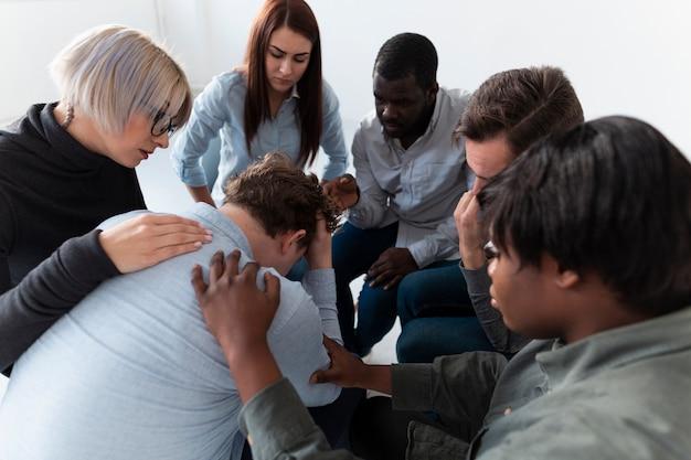 Des hommes et des femmes consolent un patient triste